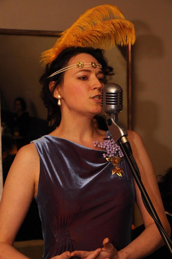 Reluctantly taking to the mic, but at least the feathers are seen!
